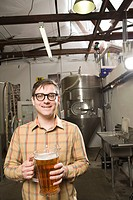 Portrait of young man in a brewery, holding a pitcher of beer