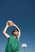Young man holding a basketball above his head about to throw the ball, image of man isolated in blue sky background