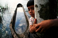 Lacandon boy and boat filled with water and reflection of the clouds in the Lacandon_jungle, Mexico, Chiapas, Lacandonen_Urwald, Naha