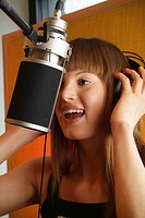 Singing young woman wearing headphones, singing into microphone of a recording studio