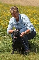 Labrador Retriever Canis lupus f. familiaris, woman with her dog on flowering meadow