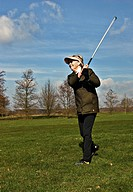 female senior at the drive on a golf course, Germany, Schleswig_Holstein