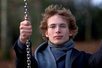 young man with glasses and curly hair,sitting on a swing, looking into the camera, Germany