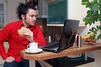 young man with burger in his hand, sitting in front of his laptop