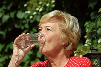 female senior sitting in the sun, enjoying a glass of water, Germany