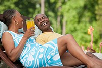 African couple relaxing in lounge chairs