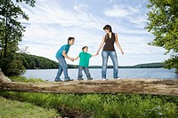 Parents helping son walk across log