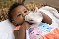 Young girl, 1, drinking a powdered formula milk, Eritrea, Africa