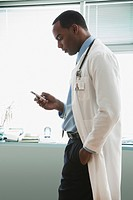 African doctor text messaging on cell phone