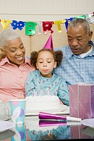 African grandparents with granddaughter at birthday party