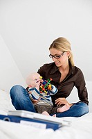 Germany, Ammersee, Diessen, Young woman with baby boy 7 months sitting on bed, portrait