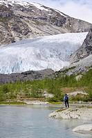 Norway, Nigardsbreen, Glacier tongue, Hiker on shore, rear view