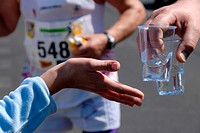 People Passing Out Cups of Water During A Marathon