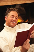 Man in front of fire place reading a book, portrait
