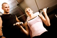 Young woman training with dumbbells with help of a trainer