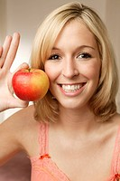 Smiling young blonde woman with apple