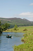 Adult man canoeing the river Don with mountain Bennachie in background, Aberdeenshire, Scotland