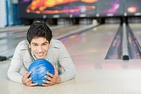 Young man lying with a bowling ball in a bowling alley