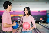 Young couple holding bowling balls in a bowling alley