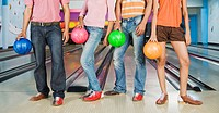 Two young couples holding bowling balls in a bowling alley