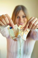 beautiful woman tearing apart a fifty Euro bill