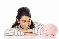 Businesswoman looking at a piggy bank