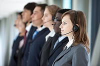 Business people standing in a row with headsets and looking away