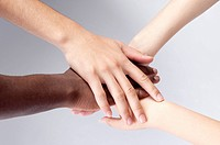Close-up of different colors of hands huddling together (thumbnail)