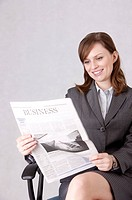 Businesswoman sitting in a chair and reading a newspaper with smile (thumbnail)