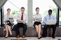 Business people reading a newspaper or using laptop to have a rest