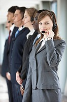 Business people standing in a row with headsets together