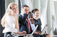 Business people sitting with laptop and using mobile phones together