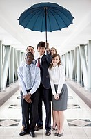 Business people standing under an umbrella and smiling
