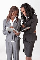 Two businesswomen standing and discussing together with smile