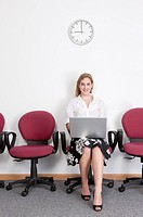 Businesswoman sitting with laptop and smiling at the camera