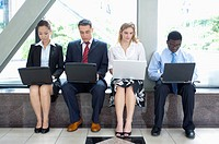 Business people sitting in a row and using laptop together