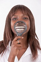 Young woman putting magnifying glass on her teeth and smiling