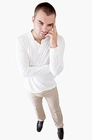 Young man looking away and thinking with head in hands (thumbnail)