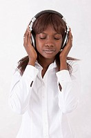 Young woman listening music with headset and closing eyes