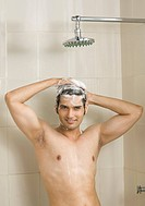 Close_up of a young man taking a shower