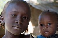 Portrait of young Gambian girl with baby sibling, Bakadagi, The Gambia
