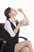 Young office lady holding a glass of water and taking medicine