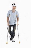 Young man standing with crutch and having adhesive bandage on head