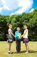 Three children holding the globe together and looking at the camera with smile