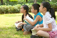 Three children sitting on the lawn with books and listening together