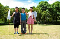 Three children standing in a row and holding butterfly nets with smile