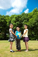 Three children standing on the lawn and holding the globe together