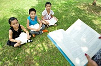 Three children sitting on the lawn, reading together