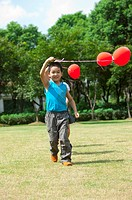 Children walking on the lawn and holding balloon together