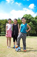 Three children standing on the lawn with a football and looking at the camera